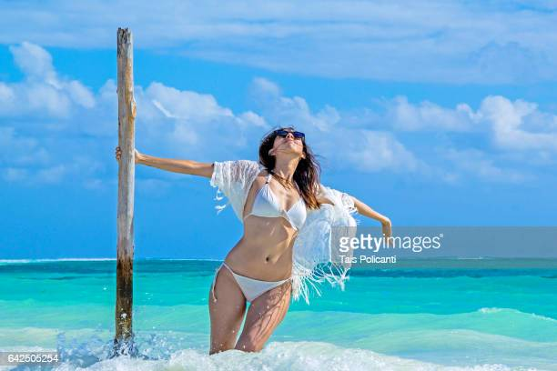 Brunette Woman enjoying a white sand caribbean beach in Mexico's Riviera Maya, Quintana Roo, Mexico