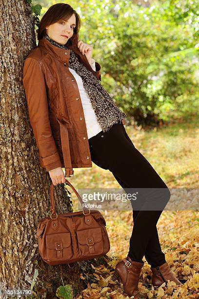 brunette femme sur arbre automne tenue - sac à main en cuir photos et images de collection
