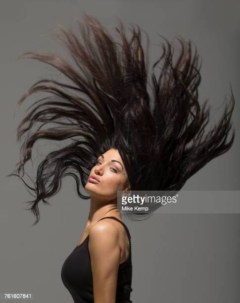 Brunette woman flipping long hair