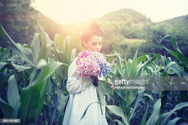Brunette Woman Holding Flowers in the Corn Field