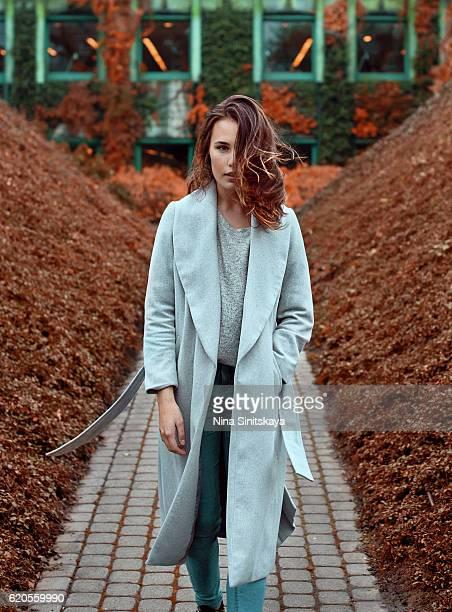 A brunette woman in long grey coat walking forward