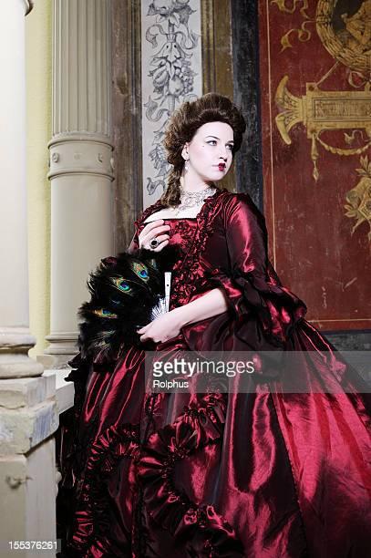 Brunette Woman in Red Baroque Dress Old Balcony