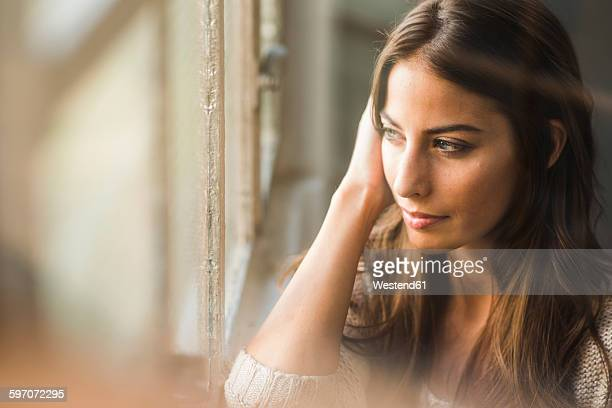 Brunette woman looking out of window