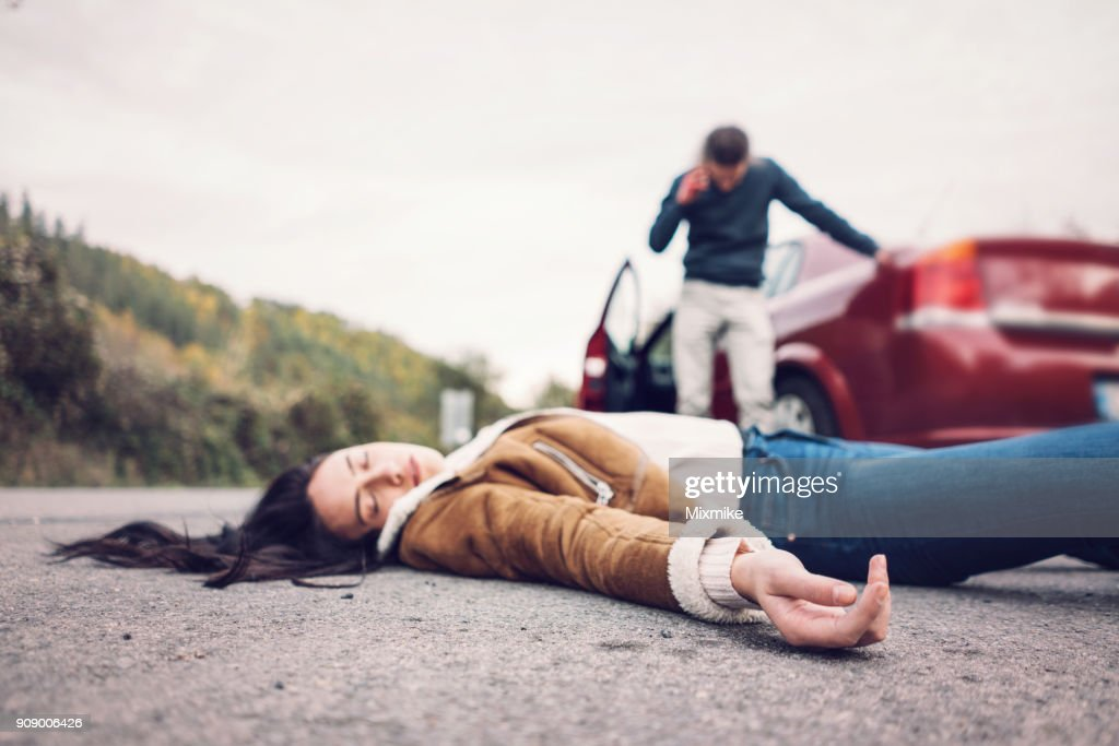 Brunette woman on the foreground lying unconscious on the road. : Stock Photo