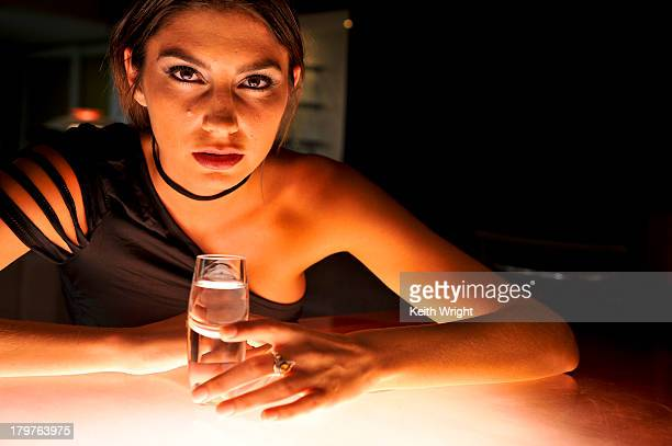 brunette woman putting poison in cocktail. - asymmetric dress stock pictures, royalty-free photos & images