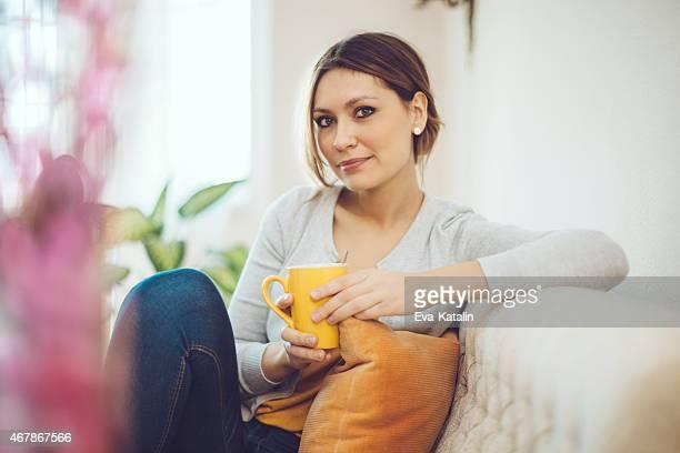 Brunette Frau Entspannung zu Haus'und Trinken Kaffee