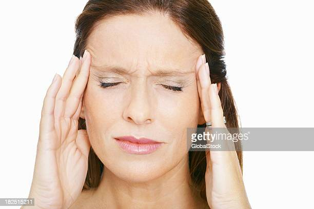 Brunette woman rubbing her temples to alleviate a headache