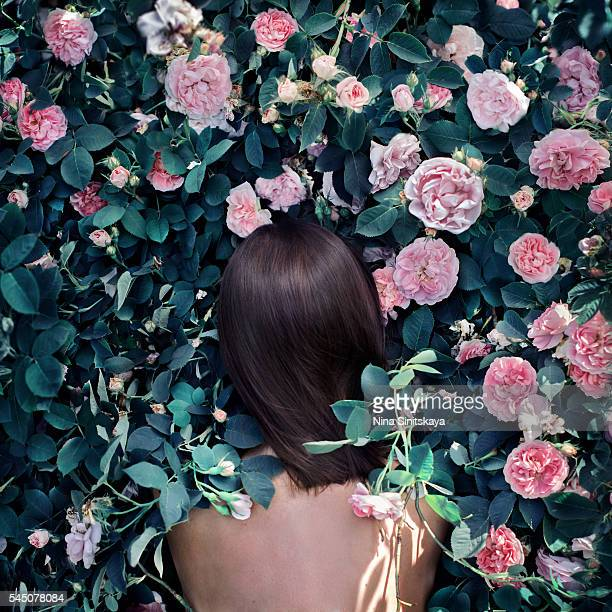 Brunette woman sitting in the bush of roses with her back to the viewer