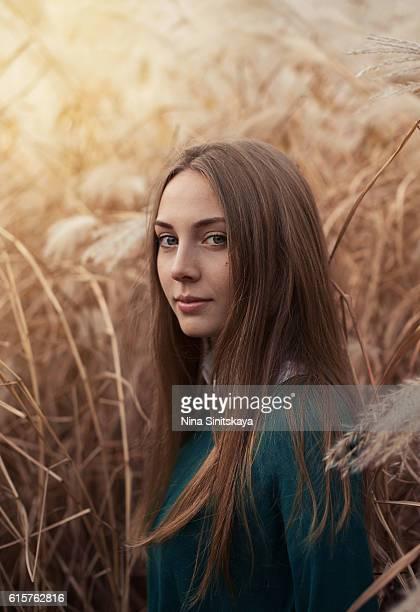 Brunette woman standing in a high browm grass