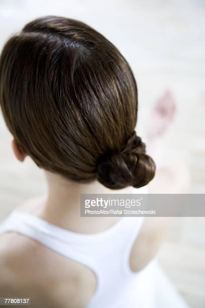 Brunette woman wearing hair in chignon, rear view