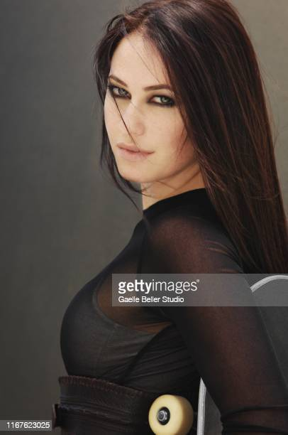 brunette woman with green eyes holding a skateboard - smokey eyeshadow stock pictures, royalty-free photos & images