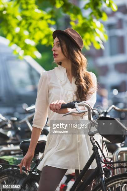 Brunette vrouw met lang haar op fiets in Amsterdam stad