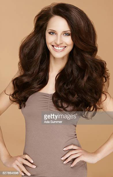 Brunette woman with wavy hair posing in front of camera