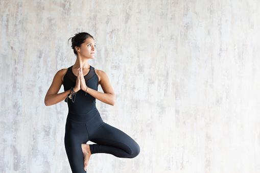 Brunette woman yoga instructor doing vrikshasana 1179814993