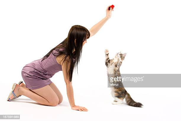 Brunette women in lilac dress playing with a cat