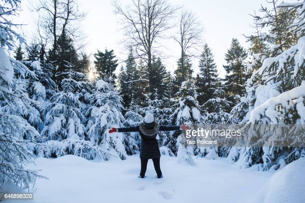 Brunette young woman enjoying a snowy forest in winter, Hoher Meissner, Hessen, Germany