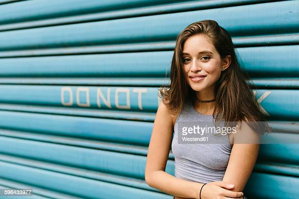Brunette young woman leaning against shutter