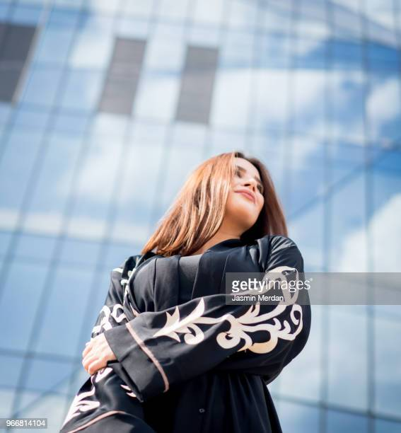 brunette young woman on city street - religious dress stock photos and pictures