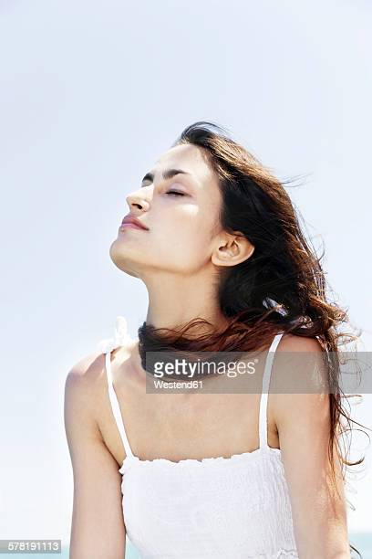 Brunette young woman with closed eyes enjoying sunshine