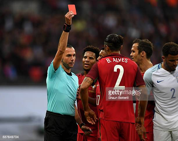 Bruno Alves of Portugal is shown a red card by referee Marco Guida and is sent off during the international friendly match between England and...