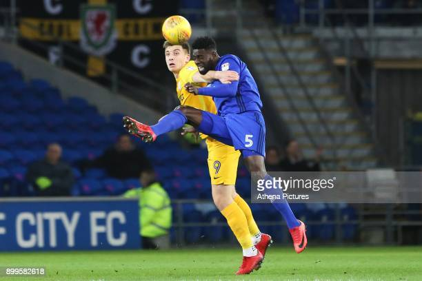 Bruno Ecuele Manga of Cardiff City heads the ball away from Jordan Hugill of Preston North End during the Sky Bet Championship match between Cardiff...