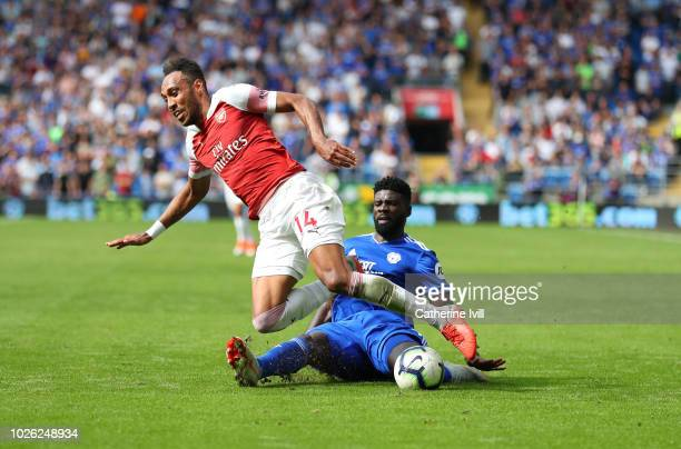 Bruno Ecuele Manga of Cardiff City tacklea PierreEmerick Aubameyang of Arsenal during the Premier League match between Cardiff City and Arsenal FC at...