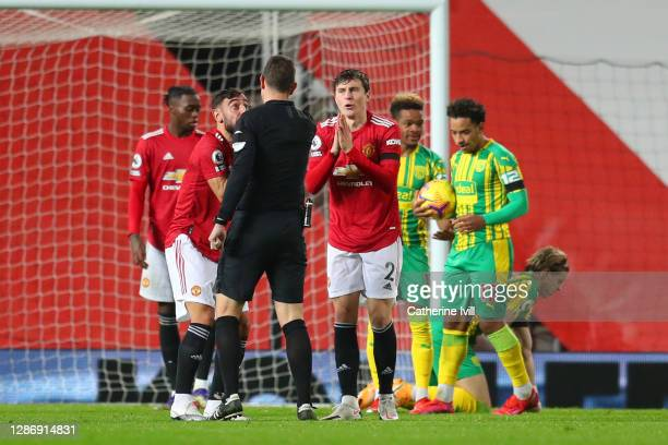 Bruno Fernandes and Victor Lindelof of Manchester United confront referee David Coote after he awards West Bromwich Albion a penalty during the...