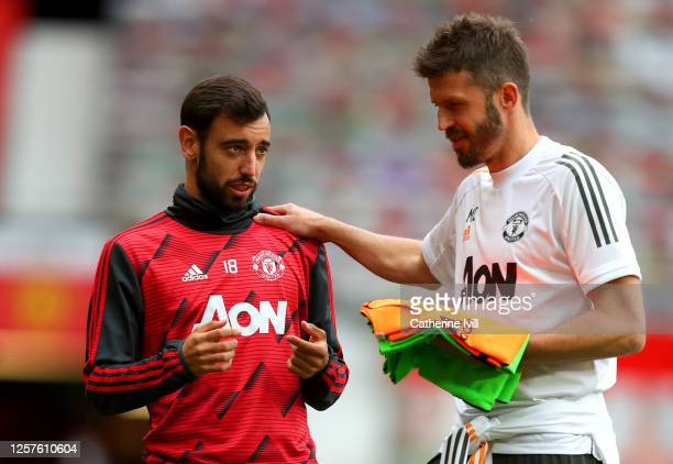 Bruno Fernandes of Manchester United and Michael Carrick, Manchester United Assistant Coach speak prior to the Premier League match between...