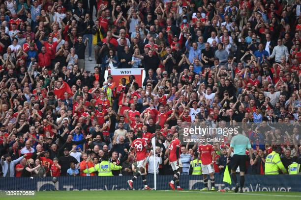 Bruno Fernandes of Manchester United celebrates after scoring their side's third goal as fans celebrate during the Premier League match between...