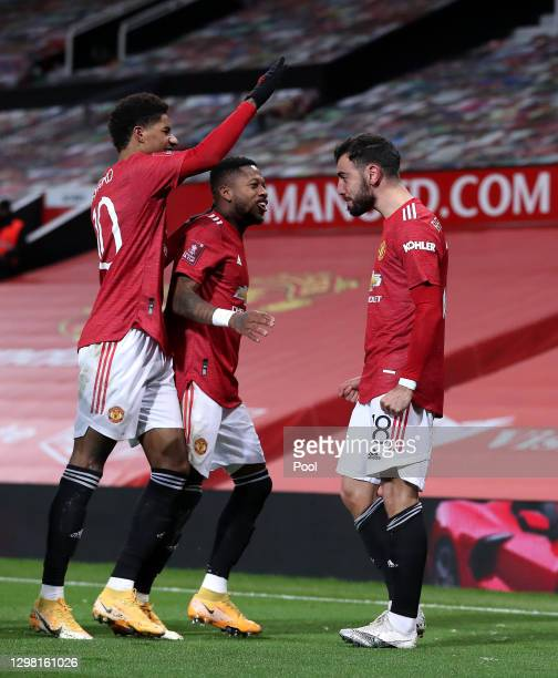 Bruno Fernandes of Manchester United celebrates with team mates Marcus Rashford and Fred after scoring their sides third goal from a free kick during...