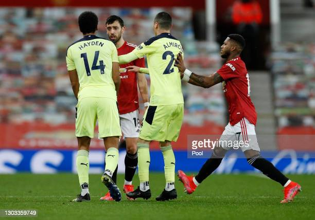 Bruno Fernandes of Manchester United clashes with Isaac Hayden and Miguel Almiron of Newcastle United during the Premier League match between...
