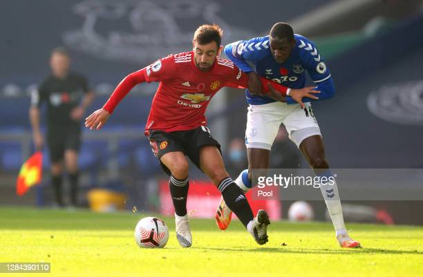 Bruno Fernandes of Manchester United is challenged by Abdoulaye Doucoure of Everton during the Premier League match between Everton and Manchester...