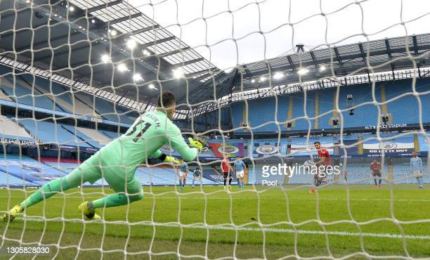 Bruno Fernandes of Manchester United scores their side's first goal from the penalty spot past Ederson of Manchester City during the Premier League...