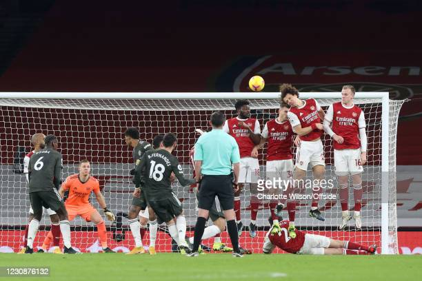Bruno Fernandes of Manchester United strikes a free-kick over the defensive wall as David Luiz of Arsenal gets a head to it during the Premier League...