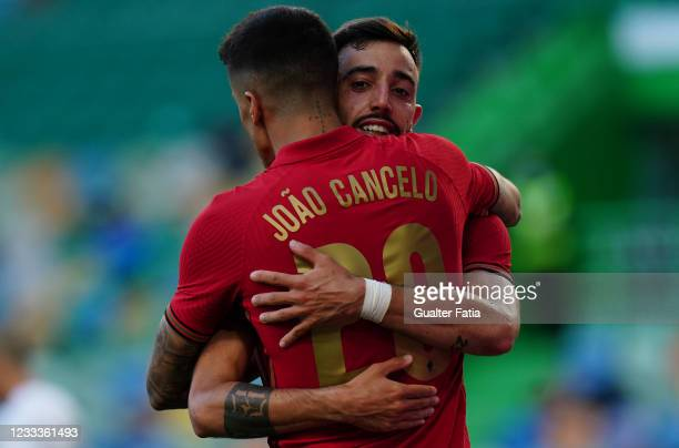 Bruno Fernandes of Portugal and Manchester United celebrates with teammate Joao Cancelo of Portugal and Manchester City after scoring a goal during...