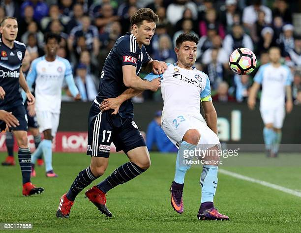 Bruno Fornaroli of Melbourne City is challenged by James Donachie of the Victory during the round 11 ALeague match between Melbourne City FC and...