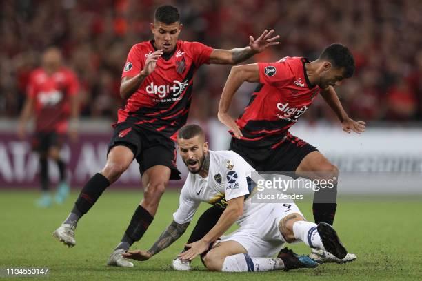 Bruno Guimaraes and Camacho of Athletico PR struggle for the ball with Dario Benedetto of Boca Juniors during a match between Athletico PR and Boca...