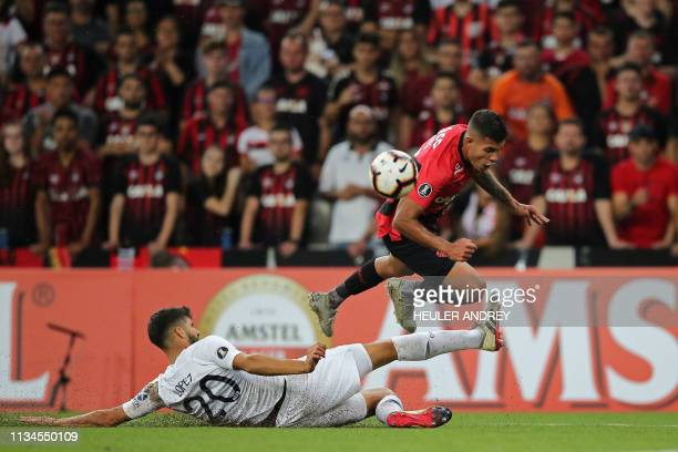 Bruno Guimaraes of Brazil's Athletico Paranaense struggles for the ball with Lisandro Lopez of Argentina's Boca Juniors during a Libertadores Cup...
