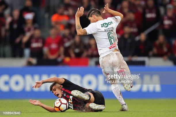 TOPSHOT Bruno Guimaraes of Brazils Atletico Paranaense falls as he vies for the ball with Ayrton of of Brazil's Fluminense during their 2018 Copa...