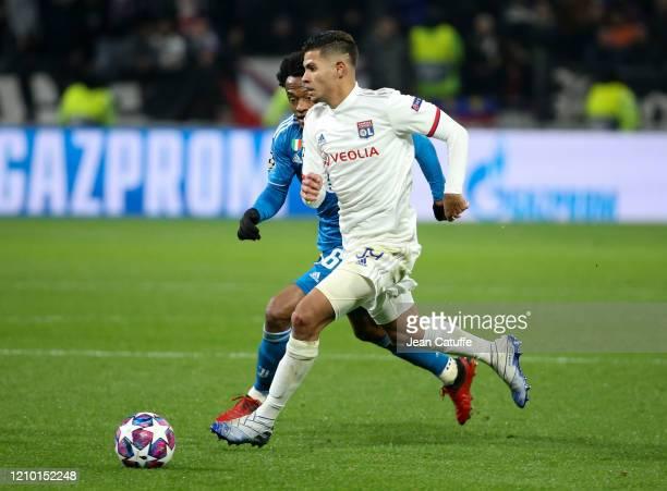 Bruno Guimaraes of Lyon Juan Cuadrado of Juventus during the UEFA Champions League round of 16 first leg match between Olympique Lyonnais and...