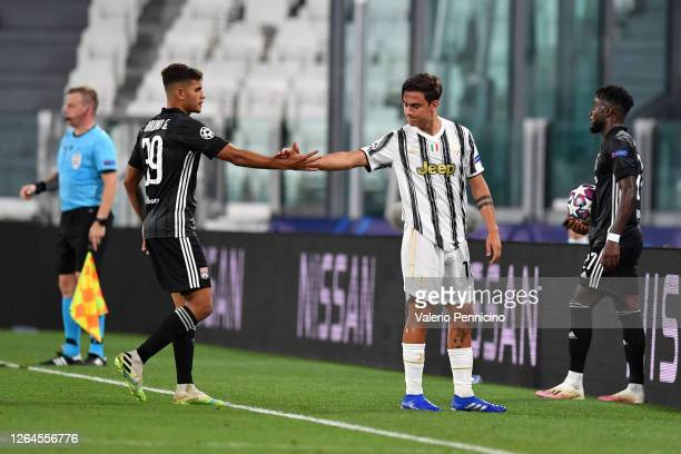 Bruno Guimaraes of Olympique Lyon shakes hands with Paulo Dybala of Juventus who leaves the pitch after getting injured during the UEFA Champions...