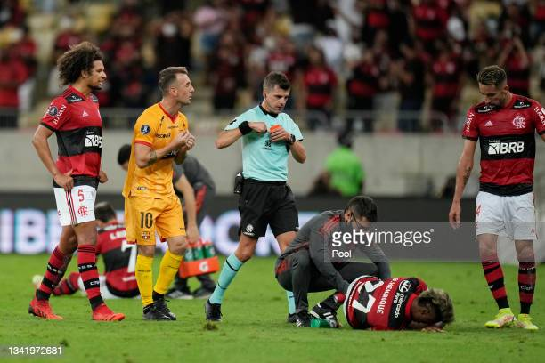 Bruno Henrique of Flamengo lies on the pitch after being injured as Referee Andrés Cunha holds a red card for Nixon Molina of Barcelona during a semi...