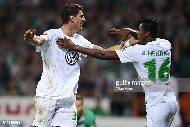 Bruno Henrique of Wolfsburg celebrates with Mario Gomez after his first goal during the Bundesliga match between Werder Bremen and VfL Wolfsburg at...