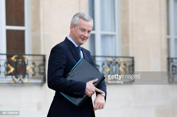 Bruno Le Maire France's finance minister points to his wristwatch as he departs following a cabinet meeting to approve labor law reforms at the...