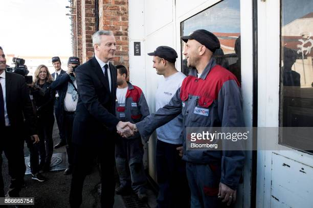 Bruno Le Maire France's finance minister shakes hands with an employee at the Alstom SA TGV railway train factory in Belfort France on Thursday Oct...