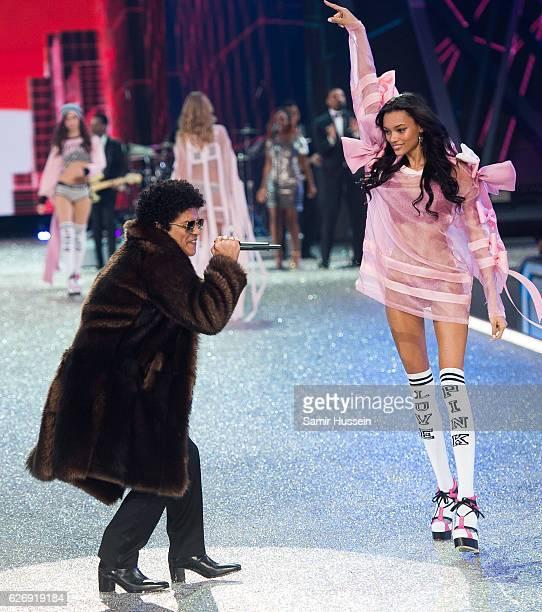 Bruno Mars performs as Lameka Fox walks the catwalk during the annual Victoria's Secret fashion show at Grand Palais on November 30 2016 in Paris...