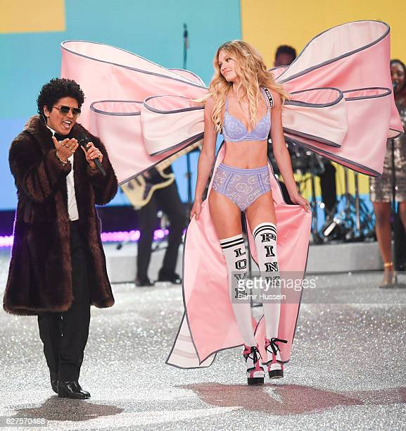 Bruno Mars performs as Maggie Lane walks the runway during the annual Victoria's Secret fashion show at Grand Palais on November 30 2016 in Paris...