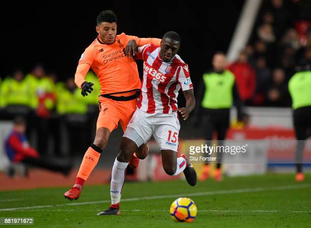 Bruno Martins Indi of Stoke City is challenged by Alex OxladeChamberlain of Liverpool during the Premier League match between Stoke City and...