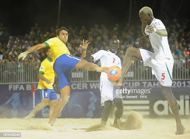 Bruno of Brazil is challenged by Mamadou Sylla and Babacar Fall of Senegal during the FIFA Beach Soccer World Cup Tahiti 2013 Group C match between...