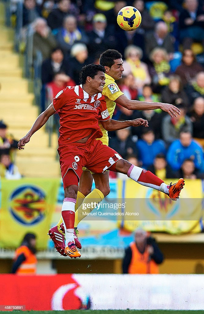 Bruno (R) of Villarreal competes for the ball in the air with Carlos Arturo Bacca of Sevilla during the La Liga match between Villarreal CF and Sevilla FC at El Madrigal on December 21, 2013 in Villarreal, Spain.